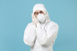 Man in white protective suit respirator mask sleep with folded hands under cheek isolated on blue background studio. Epidemic pandemic rapidly spreading coronavirus 2019-ncov medicine virus concept