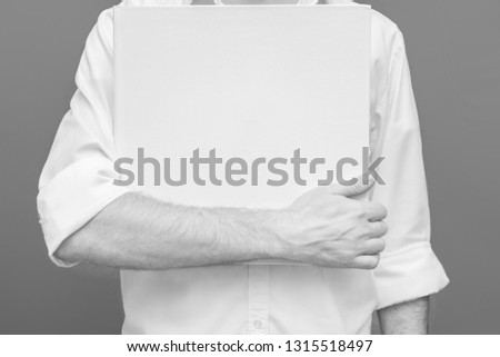 Man in white shirt holds a mockup of blank square template, book template, front view, black and white image, background, copy space, for advertising, slogan, text #1315518497