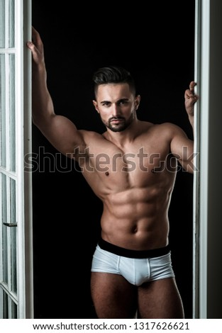Man in white shorts. Male underwear. A handsome man stands near the door. Bedroom. Sexy evening with a guy
