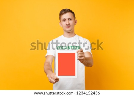Man in white t-shirt written inscription green title volunteer hold tablet pc computer with blank empty screen isolated on yellow background. Voluntary free assistance help charity grace work concept