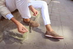 Man in white trousers sitting on the steps in the city and tying the laces on the shoes. Men's summer fashion, stylish men's shoes. Brown Perforated suede summer shoes with laces