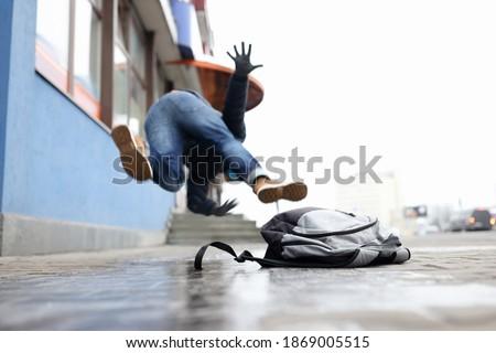 Man in winter dress slip on sidewalk with ice closeup background. Heath insurance concept Stock photo ©
