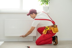 Man in work overalls using wrench while installing heating radiator in room. Young plumber installing heating system in apartment. Concept of radiator installation, plumbing works and home renovation