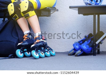 man in yellow kneecaps for protection against falling sits on a bench shod in skates for skiing, theme of sport and recreation  #1152604439
