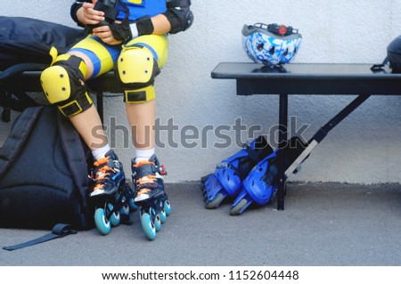 man in yellow kneecaps for protection against falling sits on a bench shod in skates for skiing, theme of sport and recreation  #1152604448