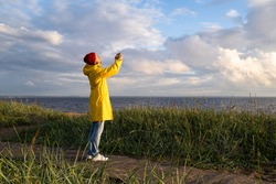 Man in yellow raincoat wear red hat standing on the beach at wooden path, looks at dramatic cloudy sky and takes photo on smartphone. Autumn season.