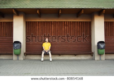man in yellow shirt sitting on bench near wooden wall