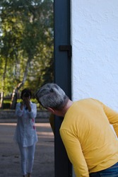 Man in yellow t-shirt looks on reflection in window at photographer standing behind