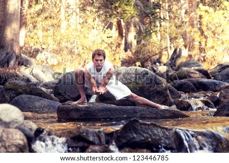 Man in yoga posture outdoors in the forest on a river.