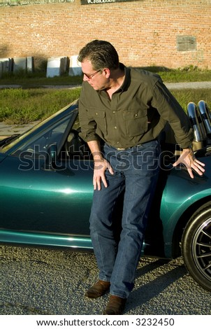 Man inclined slightly looking towards the front of his car as if concerned that his tire may be flat.