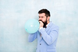 Man inflating a blue balloon. Bearded man with balloon. Happy birthday. preparation to party, celebration. Praparation to birthday party. Birthday party balloon. Party balloon. stylish event manager.