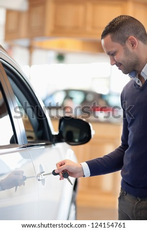 Man inserting a car key in a car