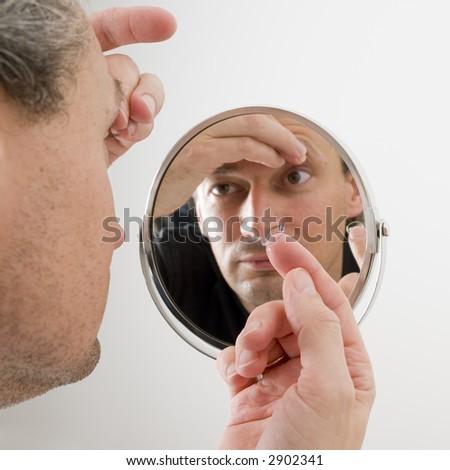 man inserting a contact lens in his eye, in front of the bathroom mirror