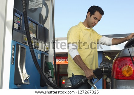 Man inserting nozzle in fuel cap of a car