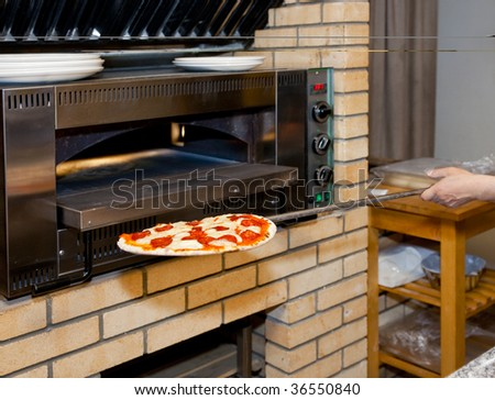 Restaurant Kitchen Oven man inserting pizza in oven, restaurant kitchen stock photo
