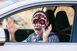 Man inside a car with a Hallowwen skull mask scaring