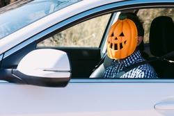 Man inside a car with a pumpkin mask of jack o lantern Hallowwen
