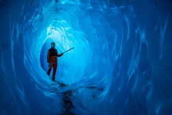 Man inside a melting glacier ice cave. Cut by water from the warming, melting glacier, the cave runs deep into the ice of the Matanuska Glacier in Alaska.