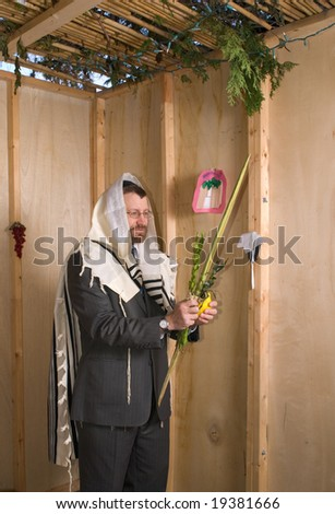 man inside a sukkah wearing prayer shawl holds lulav and etrog in the traditional manner for the jewish holiday of sukkoth
