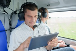 man inside the helicopter using tablet