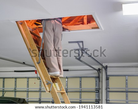 Man inspecting garage attic. Male homeowner climbing wooden pull down attic ladder stairs. Stock photo ©