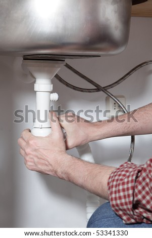 Man installing a drain for a kitchen sink