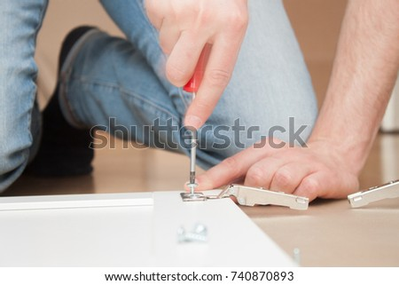 Man installing a hinge with a screwdriver #740870893