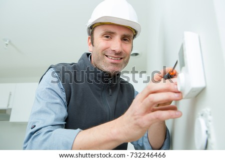 man installing a programmable room thermostat #732246466
