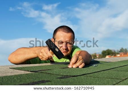 Man installing bitumen roof shingles - using a hammer and nails