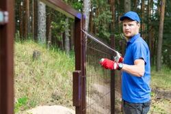 man installing brown metal fence