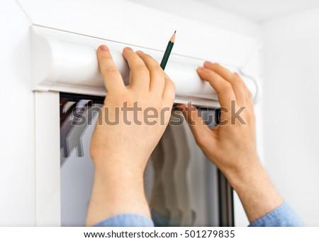 Man installing cassette roller blinds on windows. #501279835