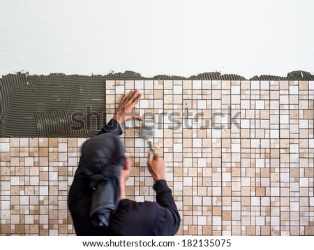 Man installing ceramic wall tile with a rubber hammer