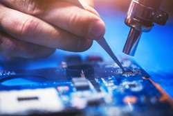 Man installing microchip on the main board of a computer. IT engineering, professional computer service.