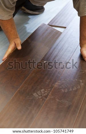 Man Installing New Laminate Wood Flooring Abstract. - stock photo