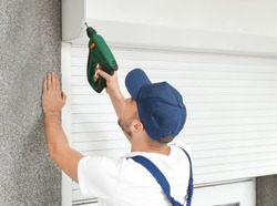 Man installing roller shutter on window