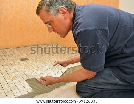Man installing sheet of mosaic ceramic tiles on shower floor