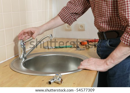 Man installing the kitchen tap and the sink