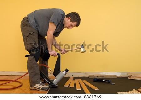 Man installing tongue and groove hardwood floor.