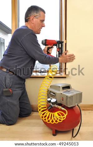Man installing window jam extensions using nail gun powered by air compressor