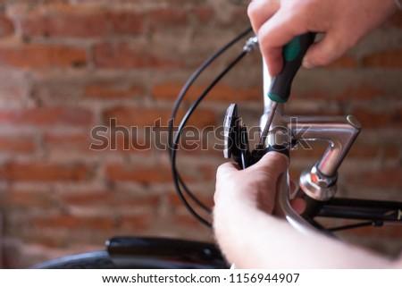 man installs a lantern screwdriver on a bicycle