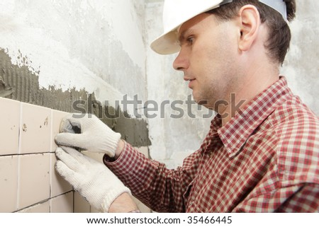 Man installs ceramic tile on a wall - stock photo