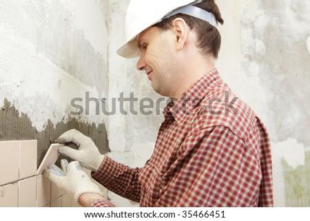 Man installs ceramic tile on a wall