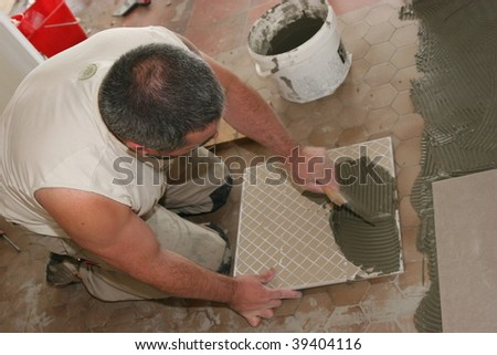 man installs ceramic tiles on the floor