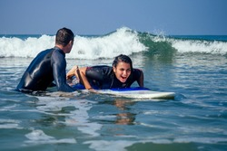 man instructor demonstrating how to paddle in the water by hands on surfboard to indian woman in surf class in Goa sea