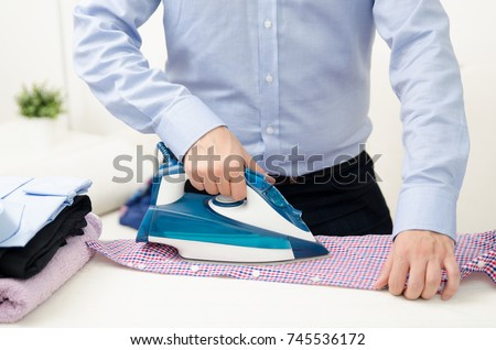 Man ironing shirt on ironing board. Steaming blue iron. Clothes ironing board household concept #745536172
