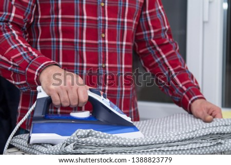 Man irons clothes on ironing board with blue iron. Housework and household concept