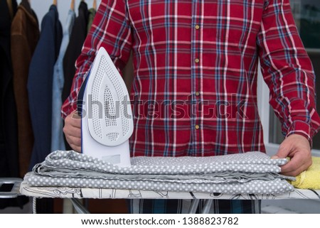 Man irons clothes on ironing board with blue iron. Housework and household concept #1388823782