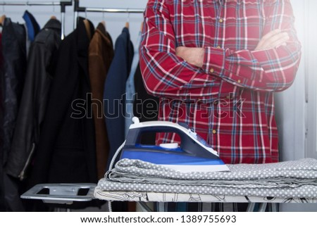 Man irons clothes on ironing board with blue iron. Housework and household concept #1389755693