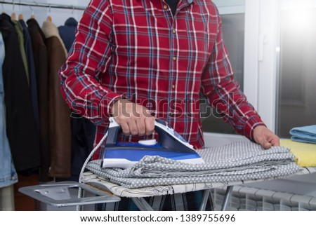 Man irons clothes on ironing board with blue iron. Housework and household concept #1389755696