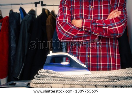 Man irons clothes on ironing board with blue iron. Housework and household concept #1389755699